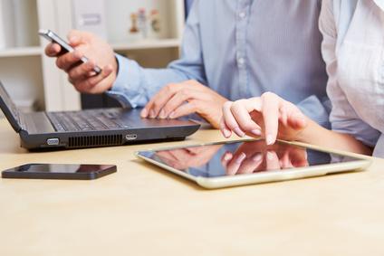 Geschäftsleute arbeiten am Schreibtisch mit Smartphones, Laptop und Tablet Computer