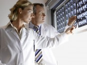Serious male and female doctors examining brain scans in hospital
