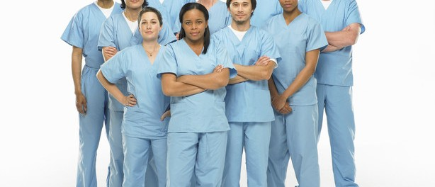Group portrait of doctors in scrubs on white background